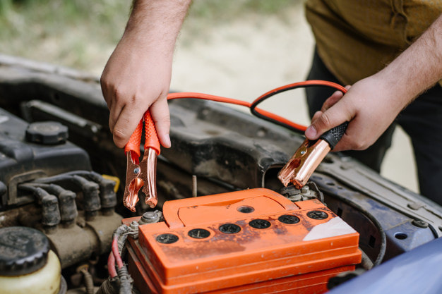 Man using jumper cables to start a dead battery that is orange
